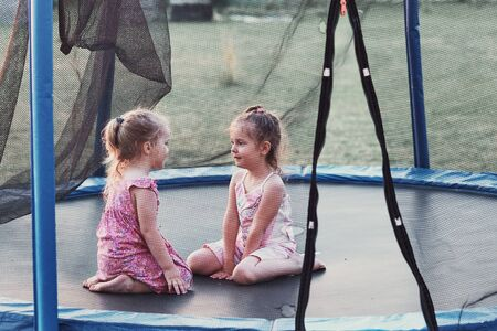 Two little cute girl talking, sitting and playing on trampoline in backyard on summer day Reklamní fotografie