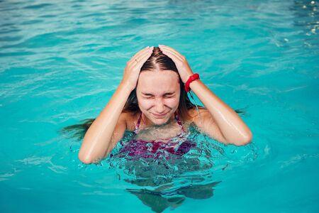Jeune femme nager et se détendre dans la piscine. Des gens francs, des moments réels, des situations authentiques