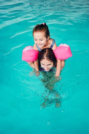 Young woman teaching to swim her younger sister and playing with her in swimming pool. Candid people, real moments, authentic situations