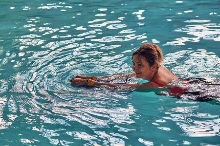 Frau schwimmen lernen, im Schwimmbad mit einem Brett üben. Offene Menschen, echte Momente, authentische Situationen