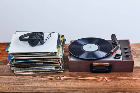 Stack of many black vinyl records, turntable vinyl player and headphones put on the stack. Classic stereo set. Candid people, real moments, authentic situations