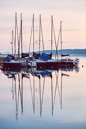 Yachts and boats moored in a harbour at sunrise. Candid people, real moments, authentic situations