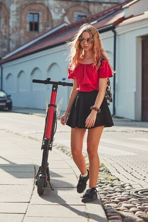 Girl using electric scooter in the street in downtown rented by using service on smartphone. Candid people, real moments, authentic situations Stock Photo