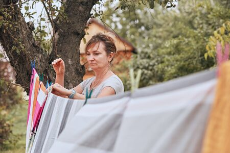 Mature woman hanging a freshly laundered bed linen on clothesline stretched between two trees in a orchard. Candid people, real moments, authentic situations Imagens
