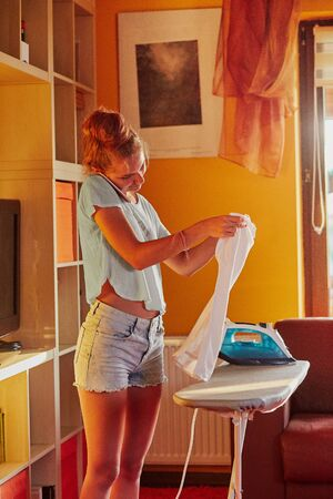 Young woman is ironing her clothes and talking on a smartphone simultaneously, standing by a ironing board in a room at home. Routine housekeeping task at home. Candid people, real moments, authentic situations