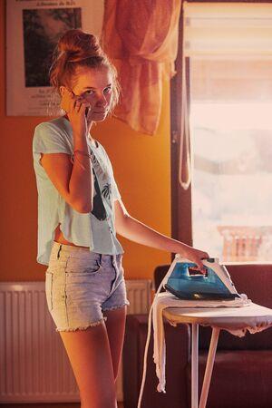 Une jeune femme repasse ses vêtements et parle simultanément sur un smartphone, debout près d'une planche à repasser dans une pièce de la maison. Tâche de ménage de routine à la maison. Des gens francs, des moments réels, des situations authentiques