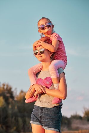 Sisters enjoying piggyback ride. Teenage girl carrying her younger sister up on the back and shoulders spending time playing together outdoors in the countryside. Candid people, real moments, authentic situations