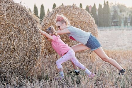 Sisters, teenage girl and her younger sister pushing hay bale playing together outdoors in the countryside. Candid people, real moments, authentic situations