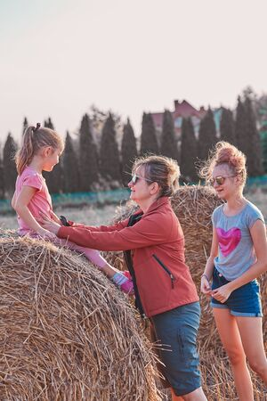 Mother and her daughters, teenage girl and her younger sister playing together on hay bale outdoors, spending vacations in the countryside. Candid people, real moments, authentic situations