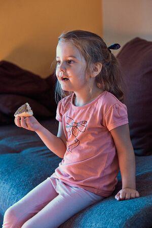 Niña linda se concentró en ver la televisión, sosteniendo un sándwich con mantequilla de chocolate, sentada en un sofá en una habitación. Gente real, situaciones auténticas
