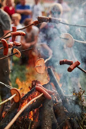 People roasting sausages and bread over a bonfire during picnic party on summer vacation day. Real people, authentic situations