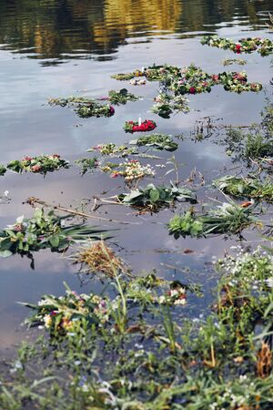 Many wreaths of flowers and herbs floating on river. Midsummer divination