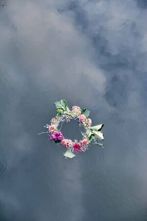Wreaths of flowers and herbs floating on river. Midsummer divination