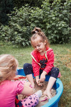 Kinder, kleine Mädchen, die am Sommertag im Sandkasten auf dem Spielplatz draußen spielen. Echte Menschen, authentische Situationen