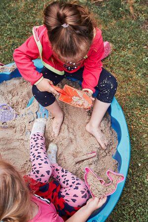 Kinder, kleine Mädchen, die am Sommertag im Sandkasten auf dem Spielplatz draußen spielen. Echte Menschen, authentische Situationen Standard-Bild