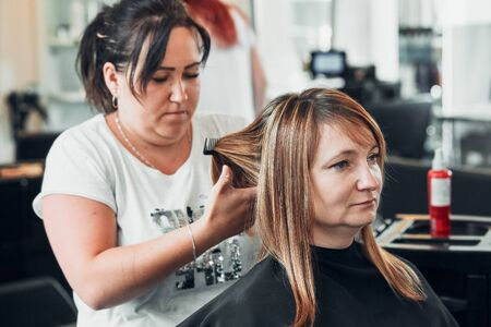 Hairdresser styling dyeing combing womans hair. Young woman working as a hairdresser in hair salon. Real people, authentic situations