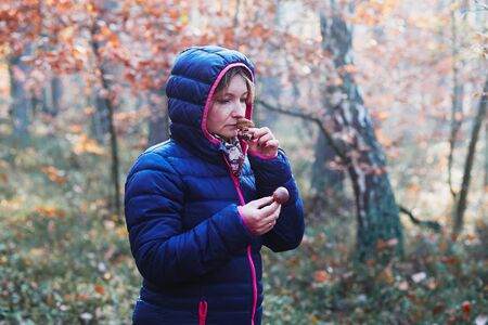 Woman smelling a mushroom picked in forest. Forest in autumn season. Colorful foliage on trees lit by morning sunlight. Natural nature forest landscape in autumn warm sunlight day. Real people, authentic situations