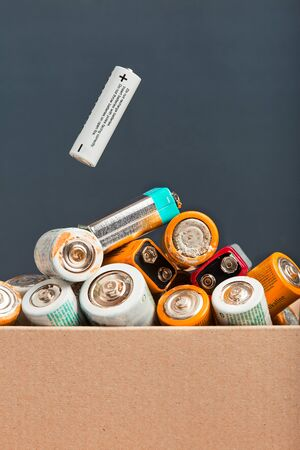 Used battery falling into a cardboard box filled with discharged batteries. Waste disposal and recycling. Front view with copy space for text
