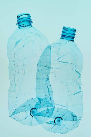 Botellas de plástico vacías aplastadas sobre fondo azul. Recogida de residuos plásticos para reciclaje. Concepto de contaminación plástica y demasiados residuos plásticos. Copiar espacio para texto