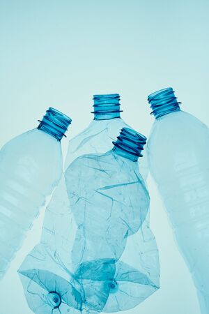 Empty plastic squashed bottles over blue background. Collecting plastic waste to recycling. Concept of plastic pollution and too many plastic waste. Copy space for text