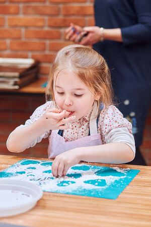 Little girl eating the icing sugar left after baking cookies. Kid taking part in baking workshop. Baking classes for children, aspiring little chefs. Learning to cook. Combining and stirring prepared ingredients. Real people, authentic situations
