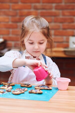 Little girl decorating her baked cookies with colorful sprinkle and icing sugar. Kid taking part in baking workshop. Baking classes for children,  aspiring little chefs. Learning to cook. Combining and stirring prepared ingredients. Real people, authentic situations Archivio Fotografico