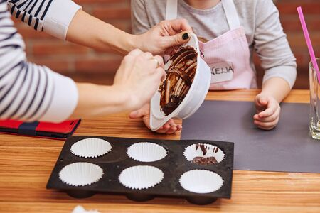 Little girl and her mom putting the melted chocolate and cocoa to cupcake. Family taking part in baking workshop. Baking classes for children,  aspiring little chefs. Learning to cook. Combining and stirring prepared ingredients. Real people, authentic situations