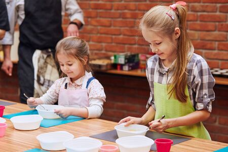 Little girls stirring the yolk with sugar. Kids taking part in baking workshop. Baking classes for children, aspiring little chefs. Girls learning to cook. Combining and stirring prepared ingredients. Real people, authentic situations Stock Photo