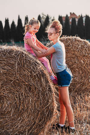 Sisters, teenage girl and her younger sister playing together on hay bale outdoors in the field in the countryside. Candid people, real moments, authentic situations Imagens