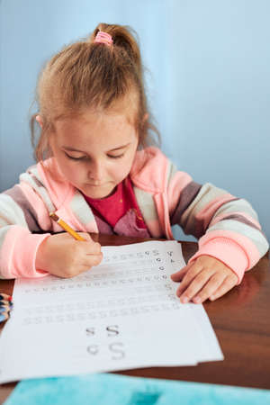 Little girl preschooler learning to write letters at school. Kid writing letters doing a school work. Concept of early education Stock fotó