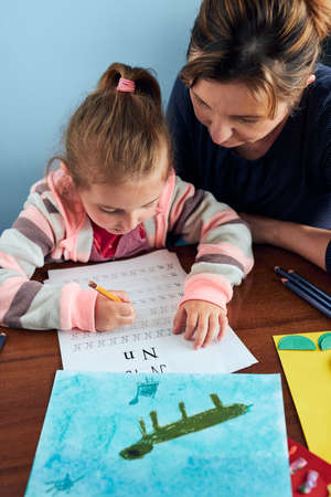 Little girl preschooler learning to write letters with help of her mother. Kid writing letters, drawing pictures, making stuff with paper, doing a homework. Concept of early education