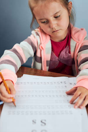 Little girl preschooler learning to write letters reluctantly. Kid writing letters, doing a school work unwillingly. Concept of early education Stock fotó - 155414220