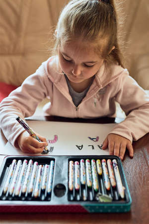 Little girl preschooler learning to write letters at home. Kid using crayons doing homework. Concept of early education Stock fotó