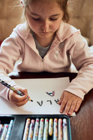 Little girl preschooler learning to write letters at home. Kid using crayons doing homework. Concept of early education 写真素材