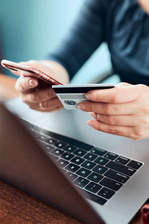 Female hands holding credit card over a keyboard of laptop sitting at a desk buying goods online from home Фото со стока