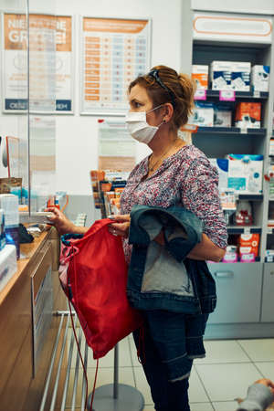 Woman shopping at pharmacy, buying medicines, wearing face mask to cover mouth and nose during pandemic coronavirus outbreak 版權商用圖片