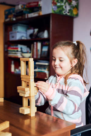 Little girl preschooler playing with wooden blocks toy building a tower. Concept of building a house