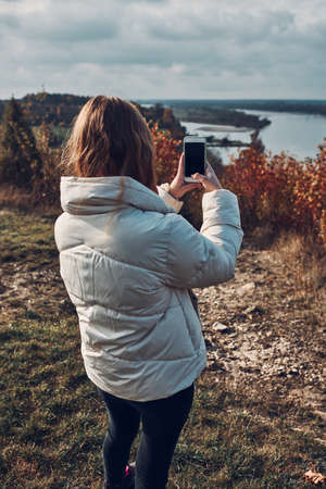Back view of young woman taking photos of landscape with smartphone during trip on autumn sunny day