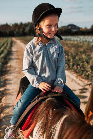 Little smiling girl learning horseback riding. 5-6 years old equestrian in helmet having fun riding a horse
