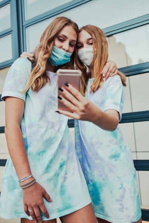 Young women girls taking selfie photos using smartphone standing at store front downtown. Girls wearing face masks to avoid virus infection and to prevent the spread of disease in time of coronavirus