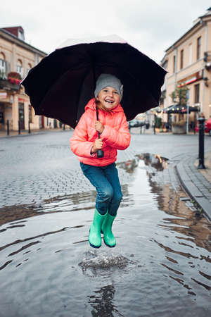 Happy smiling girl holding big umbrella jumping in the puddle during walk in a downtown on rainy gloomy autumn day