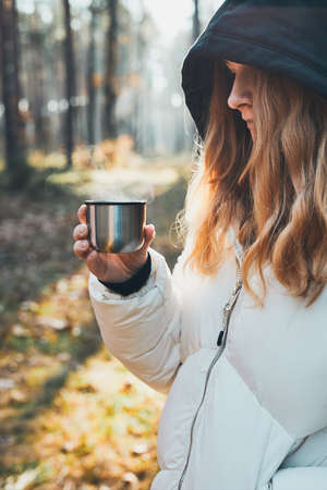 Woman in a hood having break during autumn trip holding cup with hot drink from thermos flask on autumn cold day. Active girl wandering in a forest actively spending time