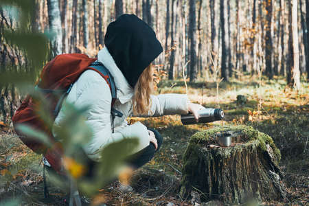 Woman having break during autumn trip pouring a hot drink from thermos flask on autumn cold day. Active women wandering in a forest actively spending time