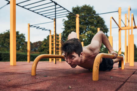 Young shirtless man bodybuilder doing push-ups on a parallel bars during his workout in a modern calisthenics street workout park 版權商用圖片