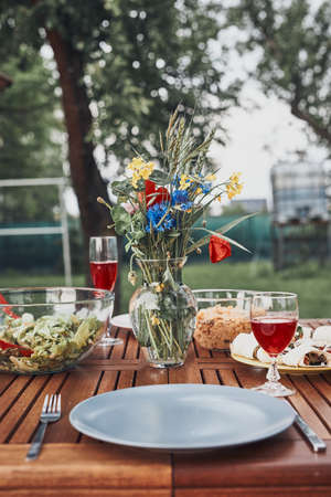 Dinner in an apple orchard garden on wooden table with salads and wine decorated with flowers. Close up of table with food prepared for family dinner 版權商用圖片