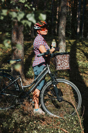 Active woman spending free summer vacation time on a bicycle trip in a forest. Woman wearing bicycle helmet and gloves holding bike with basket and drinking a water from bottle 版權商用圖片