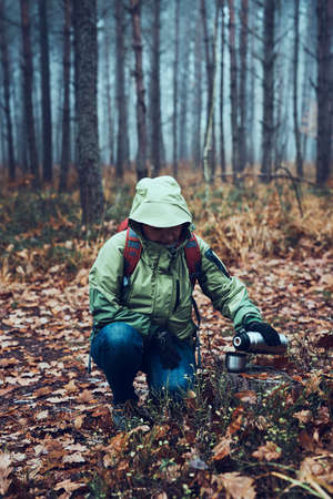 Woman with backpack having break during autumn trip on autumn cold day pouring a hot drink from thermos flask. Active middle age woman wandering around a forest actively spending time