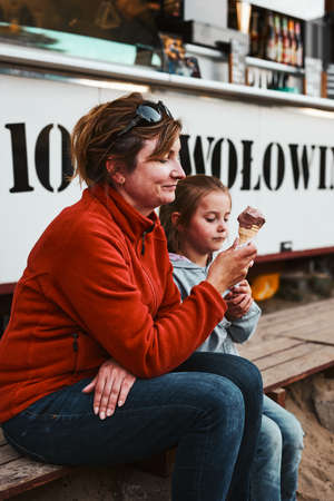 Mother and her daughter eating ice cream sitting on a step in front of food truck during summer vacations
