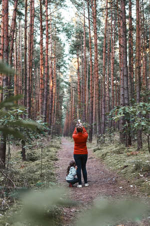 Mother and her little daughter walking in a forest during summer vacation trip. Woman taking photos using smartphone. Family spending time together outdoors in nature