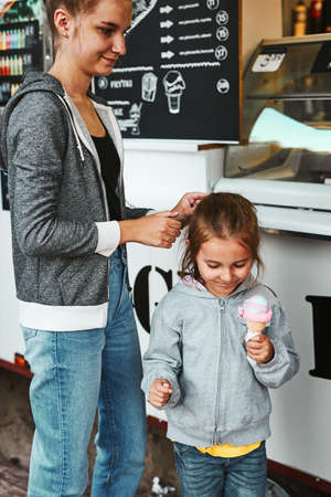 Teenage girl and her younger sister buying ice cream in a food truck during summer vacations. Spending family time on summer day